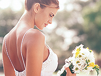 Bride with flowers showered in bright light
